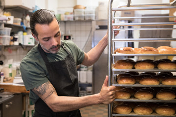 Man moving rack with breads in bakery