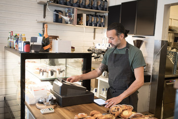 Confident mature male owner using cash register at checkout in bakery