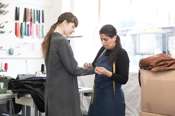 Mature female entrepreneur adjusting overcoat sleeve for young customer at Laundromat