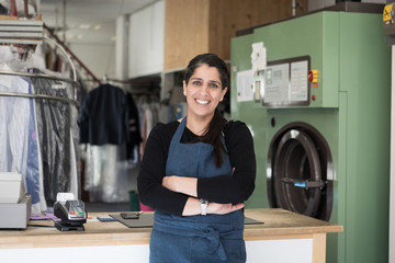 Portrait of smiling confident mature female dry cleaner standing with arms crossed at Laundromat