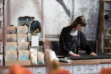Confident young female owner looking at wrapping paper on counter in store