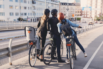 Rear view of man taking selfie with female friends with bicycles on street