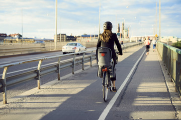 Rear view of businesswoman cycling on bridge against sky