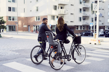 Rear view of business coworkers with bicycles crossing street in city