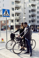 Business coworkers standing with bicycles on sidewalk in city