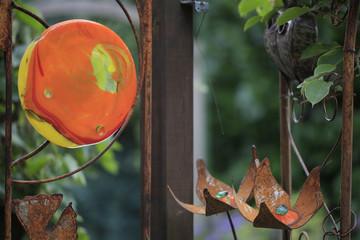 Runde Glasform mit rostfarbenen Gingkoblättern als Gartendekoration