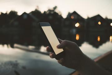 Cropped image of man text messaging through smart phone at lake