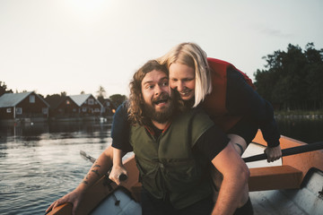 Happy couple enjoying in boat on lake against sky