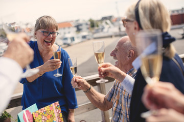Cheerful senior woman toasting champagne flute with friends on restaurant patio