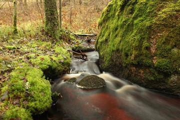 clear stream runs a large stone, wilderness landscape, long exposure