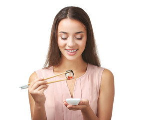 Beautiful young woman with sushi roll on white background