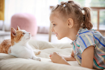 Cute little girl with cat at home