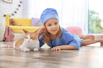 Cute little girl dressed as doctor with cat at home