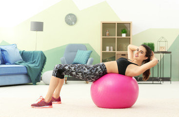 Beautiful young woman doing exercises with fitness ball at home