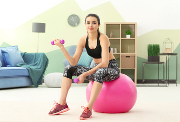 Beautiful young woman doing exercises with dumbbells at home