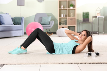 Beautiful young woman doing exercises at home