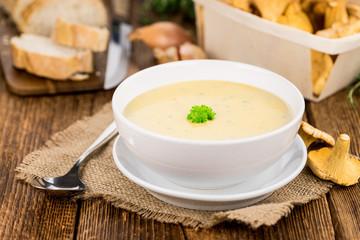 Chanterelle Soup on wooden background; selective focus