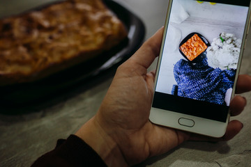 A picture of a pie on the smartphone in lady's arm
