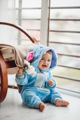 Little baby in blue suit looks like a Stitch sitting on the floor before bright window