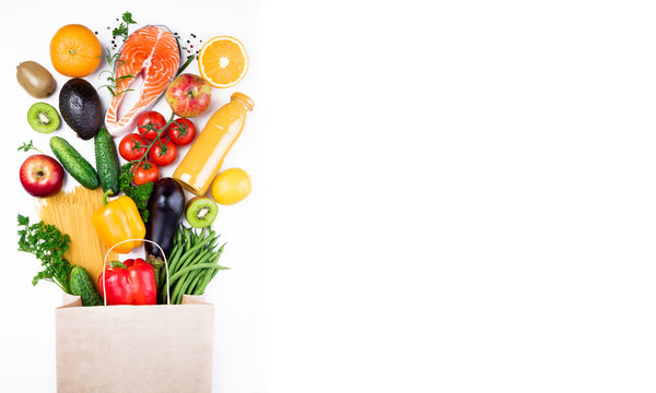 Healthy food background. Healthy food in paper bag fish, vegetables and fruits on white. Shopping food supermarket concept. Long format with copy space