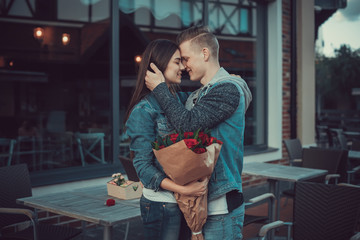 Date of two lovers. Teenagers walk around the city. A loving couple is spending a vacation together. The man gives the girl flowers.