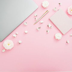Feminine desktop with laptop, notebook and white flowers on pink background. Top view. Flat lay lifestyle concept.