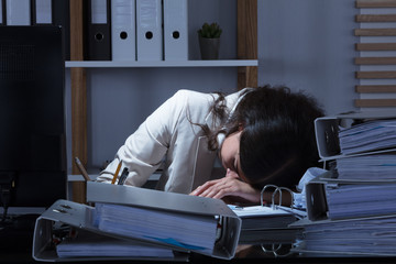 Businesswoman Leaning Head On Desk While Working Late