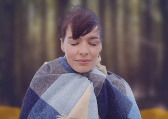 Woman's face in forest with leaves with blanket
