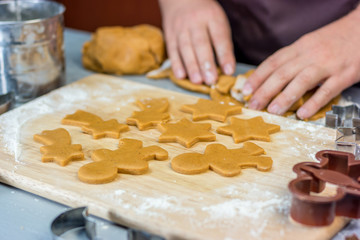 Woman makes christmas gingerbread cookies. Dough and metal cutters on wooden table, horizontal