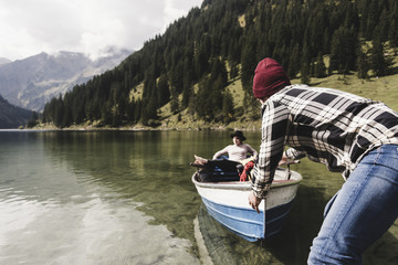 Austria, Tyrol, Alps, couple with rowing boat on mountain lake