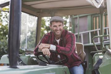Portrait of confident farmer on tractor