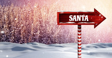 Santa text on Wooden signpost in Christmas Winter landscape