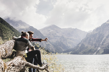 Austria, Tyrol, Alps, couple sitting on tree trunk at mountain lake taking selfie