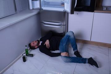 Man Lying On Floor In Kitchen