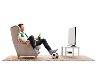 Young man with a scarf and a bottle of beer sitting in an armchair and watching football on TV