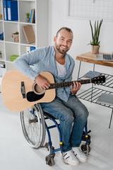 man on wheelchair playing guitar