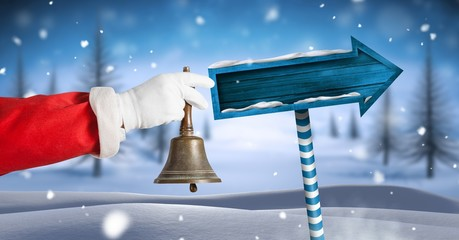 Santa ringing bell and Wooden signpost in Christmas Winter