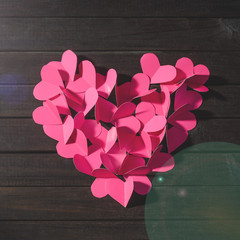 Cut out from paper red hearts laid out in the form of a big heart top view