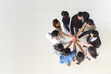 top view of business multi-ethnic partners teamwork, team join hand together at office, synergy concept