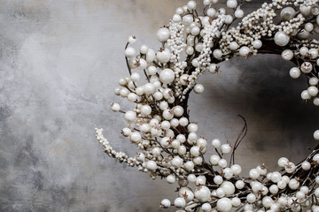 christmas wreath of branches with berries on a gray background with divorces on the right