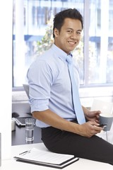 Smiling businessman sitting on desk in office