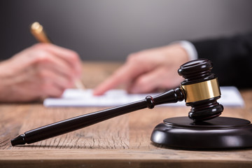 Close-up Of A Gavel On Wooden Desk