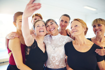 Smiling friends taking selfies together in a dance studio