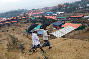 Rohingya refugee walks with an umbrella in the Palong Khali refugee camp in Cox's Bazar