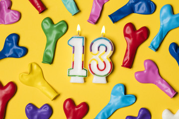 Number 13 candle with party balloons on a bright yellow background