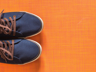 Blue sneakers on orange background
