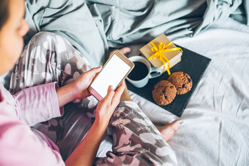 woman drink and eat cookies in the bed gift box near her