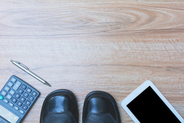Office table with pen, calculator, shoes and smart-phone. View from above with copy space.
