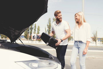 A young guy and a girl put luggage in the trunk of their electric car.
