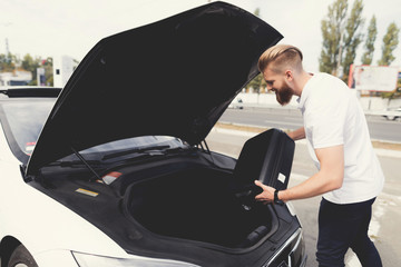 A young guy put luggage in the trunk of their electric car.